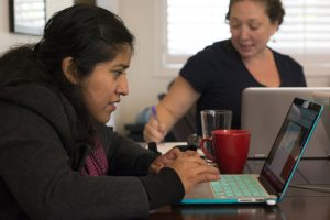 Brenda Nicolas, left, works on updating the Mapping Indigenous LA website with information on Latin American Indigenous diaspora communities with Mishuana Goeman, right